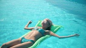 Mulher bonita nova que encontra-se no colchão de ar na piscina Fotos de Stock
