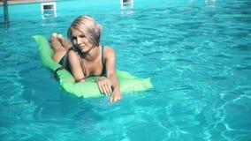Mulher bonita nova que encontra-se no colchão de ar na piscina imagens de stock