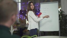 Mulher bonita nova que escreve na estratégia da placa do negócio do trabalho, explicando suas ideias ao colega masculino no escri filme