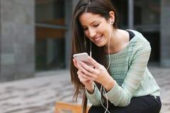 Mulher bonita nova que escuta a música com telefone dentro fora fotografia de stock royalty free
