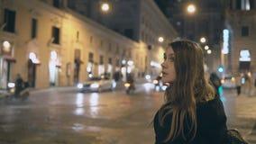 A mulher bonita nova que está perto da estrada do tráfego na noite e que olha ao redor, encontra a maneira no smartphone imagens de stock royalty free