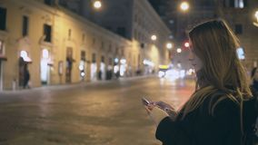 A mulher bonita nova que está perto da estrada do tráfego na noite e que olha ao redor, encontra a maneira no smartphone imagem de stock royalty free