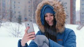 Mulher bonita nova que fala no vídeo no telefone celular no inverno Enfrente o close-up video estoque