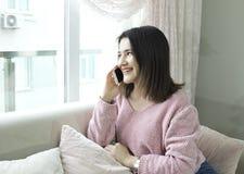 Mulher bonita nova que fala pelo telefone celular no sofá imagem de stock royalty free