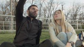 Mulher bonita nova que fala a um homem novo que senta-se no gramado Pares novos de estudantes que discutem que sentam-se no filme
