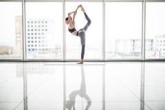 Mulher bonita nova que faz esticando o exercício na esteira da ioga Conceito da aptidão, do esporte, do treinamento e do estilo d foto de stock
