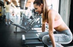 Mulher bonita nova que faz exercícios no gym imagens de stock