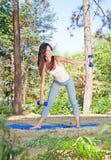 Mulher bonita nova que faz exercícios no parque foto de stock royalty free