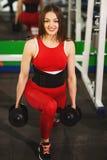 Mulher bonita nova que faz exerc?cios com peso no gym A menina de sorriso contente est? apreciando com seu processo do treinament imagens de stock