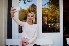 Mulher bonita nova que faz o autorretrato no telefone celular ao descansar no café do passeio uma bebida da bebida, fotos de stock royalty free