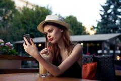Mulher bonita nova que faz o selfie que senta-se em um café em uma rua do verão na cidade imagem de stock royalty free