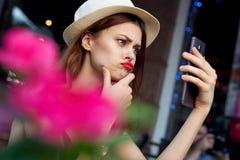 Mulher bonita nova que faz o selfie que senta-se em um café na rua foto de stock royalty free