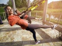 Mulher bonita nova que faz o treinamento da aptidão com correias da suspensão Foto de Stock Royalty Free