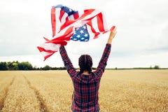Mulher bonita nova que guarda a bandeira dos EUA Imagens de Stock