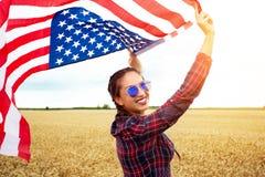 Mulher bonita nova que guarda a bandeira dos EUA Fotografia de Stock Royalty Free