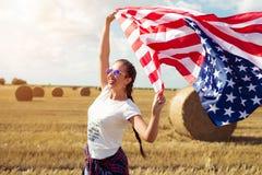 Mulher bonita nova que guarda a bandeira dos EUA Imagem de Stock Royalty Free