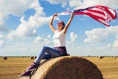 Mulher bonita nova que guarda a bandeira dos EUA Fotos de Stock