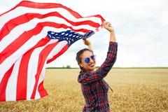 Mulher bonita nova que guarda a bandeira dos EUA Imagem de Stock