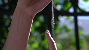 Mulher bonita nova que guarda a cruz de prata nas mãos Religião da cristandade filme