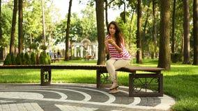 Mulher bonita nova que guarda o telefone celular e que senta-se no banco no parque do verão filme