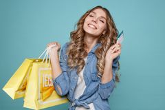 Mulher bonita nova que guarda sacos de compras e um cartão de crédito imagem de stock