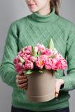 Mulher bonita nova que guarda um ramalhete das tulipas em uma caixa de presente cores cor-de-rosa em um caixa ou ramalhete Presen Fotografia de Stock