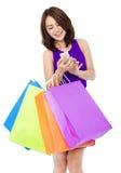 Mulher bonita nova que guarda um telefone celular para comprar em linha Fotografia de Stock Royalty Free