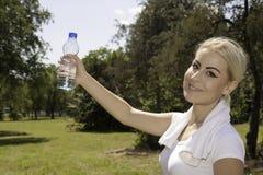 Mulher bonita nova que guarda uma garrafa da água Fotografia de Stock Royalty Free