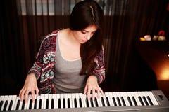 Mulher bonita nova que joga no piano Foto de Stock