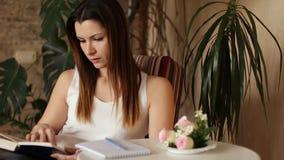 Mulher bonita nova que lê um livro e que toma notas Mulher que lê um livro que senta-se em uma cadeira video estoque