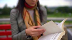 Mulher bonita nova que lê um livro que senta-se em um banco fora em um parque no verão Feche acima do livro 4 K filme