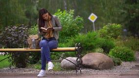 Mulher bonita nova que lê um livro que senta-se em um banco fora em um parque no verão 4 K video estoque