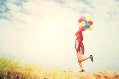 Mulher bonita nova que mantém o balão muito feliz no ai fresco foto de stock