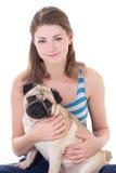 Mulher bonita nova que mantém o cão do pug isolado no branco Fotos de Stock Royalty Free