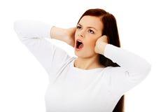 Mulher bonita nova que obstrui suas orelhas e que grita Fotos de Stock