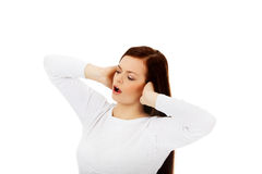 Mulher bonita nova que obstrui suas orelhas e que grita Fotografia de Stock Royalty Free