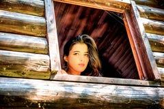 Mulher bonita nova que olha fora da janela imagem de stock royalty free