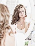 Mulher bonita nova que olha sua cara no espelho Fotografia de Stock