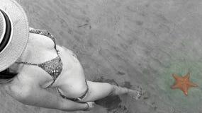 Mulher bonita nova que olha uma estrela do mar na água de Playa Estrella na ilha dos dois pontos, del Toro de Bocas, Panamá Fotografia de Stock Royalty Free