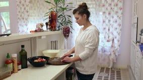 Mulher bonita nova que prepara uma salada na cozinha cebolas video estoque