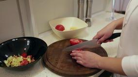 Mulher bonita nova que prepara uma salada na cozinha Tomates filme