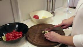 Mulher bonita nova que prepara uma salada na cozinha Tomates e pimentas de sino video estoque