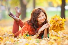 Mulher bonita nova que relaxa no parque do outono fotos de stock royalty free