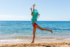 Mulher bonita nova que salta na praia foto de stock royalty free