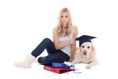 A mulher bonita nova que senta-se com o cão no chapéu do estudante isolou o foto de stock royalty free