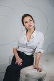 Mulher bonita nova que senta-se contra o branco Imagem de Stock Royalty Free