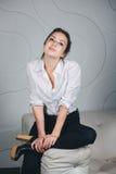 Mulher bonita nova que senta-se contra o branco Foto de Stock Royalty Free