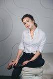Mulher bonita nova que senta-se contra o branco Fotos de Stock Royalty Free