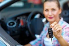 Mulher bonita nova que senta-se em um carro convertível com as chaves dentro Fotografia de Stock Royalty Free