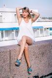 Mulher bonita nova que senta-se em uma terraplenagem do granito foto de stock